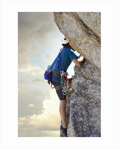 Young man rock climbing up a vertical cliff by Corbis