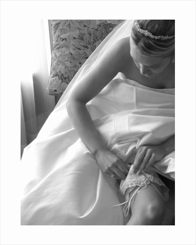 Bride Pulling Up Garter by Corbis