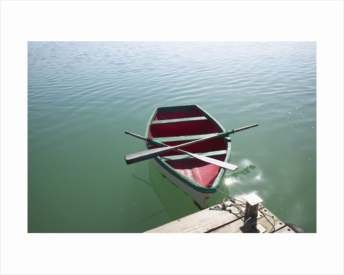 Rowing boat moored at the end of a jetty by Corbis