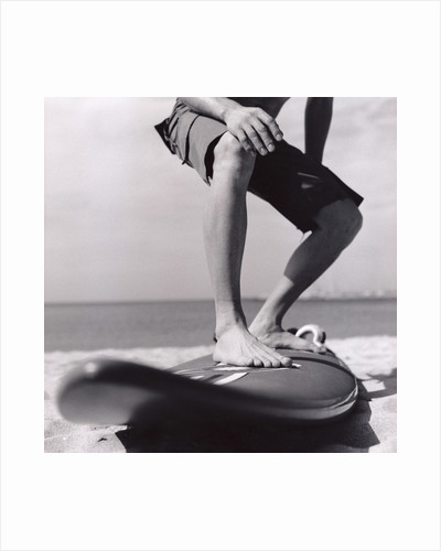 Young Man Standing on Surfboard on the Beach by Corbis