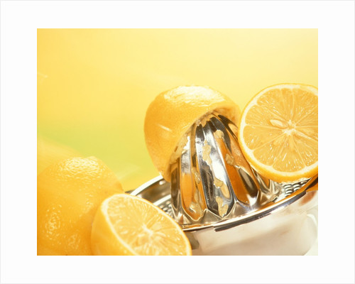 Lemons and a fruit-press by Corbis