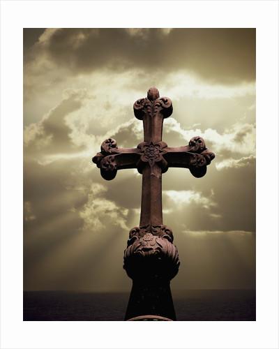 Sunbeams Backlighting Cross by Corbis