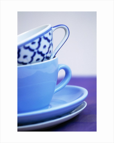 Coffee cups and saucers by Corbis