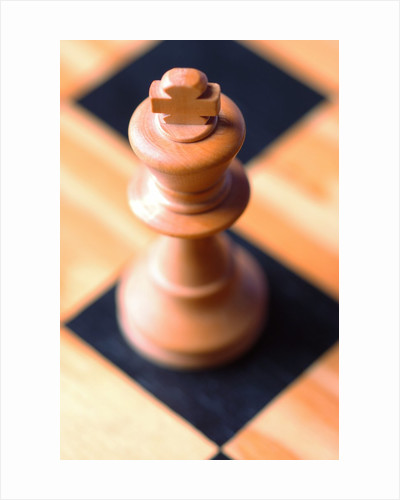 King chess piece on chessboard by Corbis