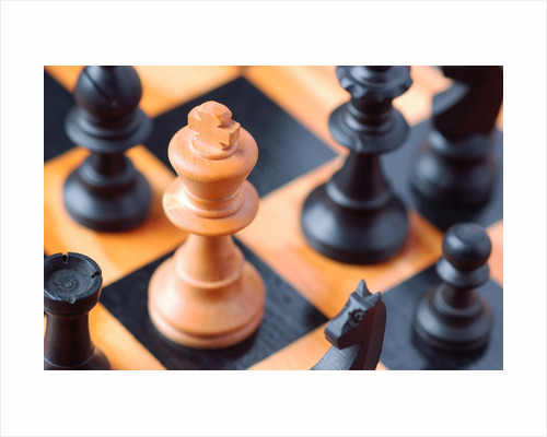 Chess pieces on chessboard by Corbis