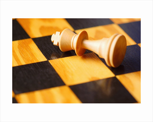 King chess piece lying on chessboard by Corbis