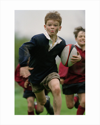 Boy Running with Rugby Ball by Corbis