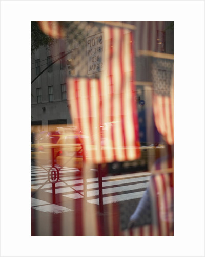 Yellow taxis in intersection reflected in window with American flags by Corbis
