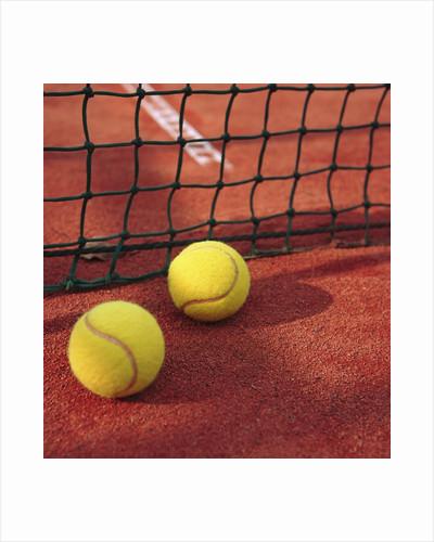 Tennis balls and net by Corbis