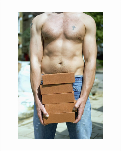 Construction Worker Carrying Bricks by Corbis