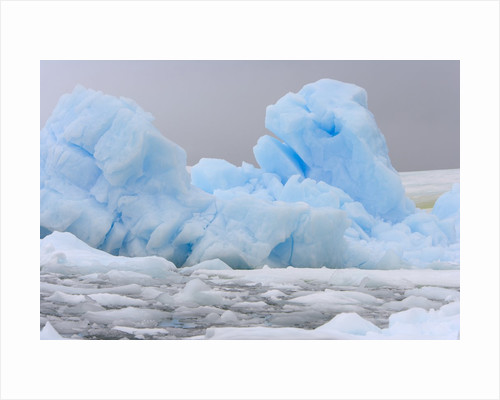 Blue Iceberg Floating Amid Ice Chunks by Corbis