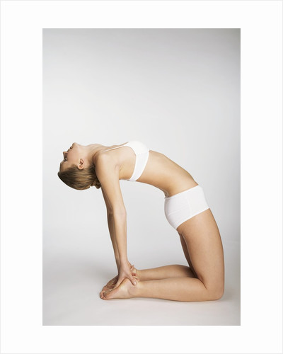 Woman stretching in camel pose by Corbis