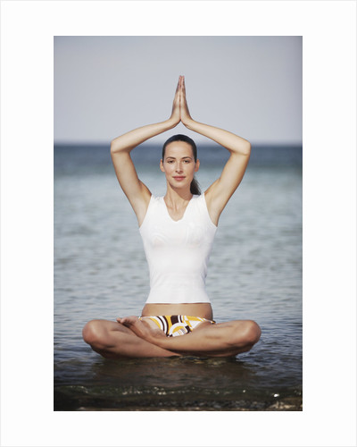 Woman meditating in the ocean by Corbis