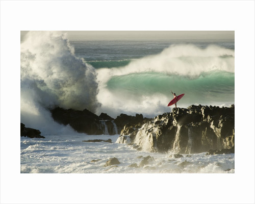 Surf Crashing near Surfer on Boulders by Corbis