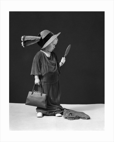 1930s 1940s Girl Playing Dress-Up Looking At Herself In Hand Mirror by Corbis