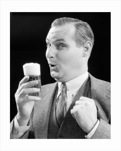 1930s Man Holding Full Foamy Glass Of Beer Making A Funny Face With His Thumb Hooked Confidently Under His Vest by Corbis