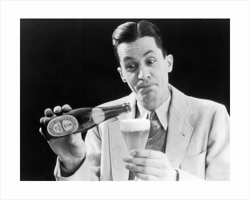 1930s Man Pouring Beer From Bottle Into Glass Look Of Anticipation Wearing Suit Tie Sweater by Corbis