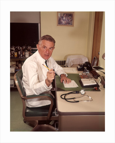 1960s Man Doctor Pointing Gesturing With Pencil Seated At Desk In Office by Corbis