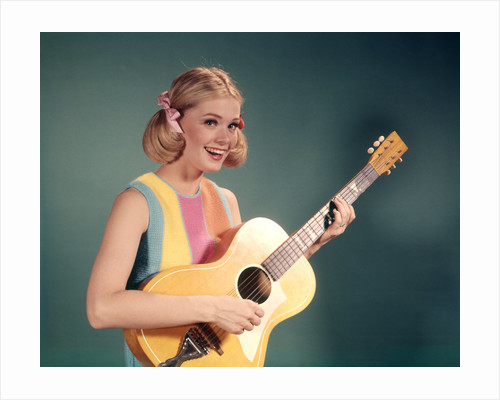 1960s Perky Young Teenager Folk Singer Playing Guitar by Corbis