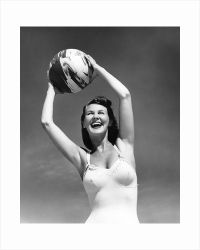 1940s Woman In White Bathing Suit Holding A Beach Ball Over Her Head Outdoor by Corbis