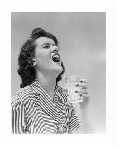 1940s Woman Gargling Medicine Holding A Glass Indoor by Corbis