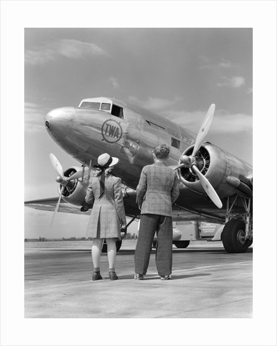 1940s rear view of boy and girl standing together looking at propeller airplane outdoor by corbis