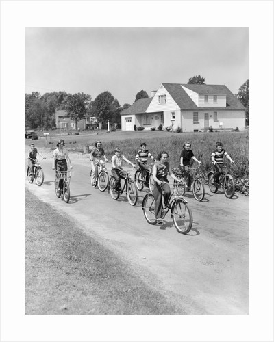 1950s 8 Kids Boys and Girls Ride Bicycles On Country Rural Road Lane Fun House In Background by Corbis