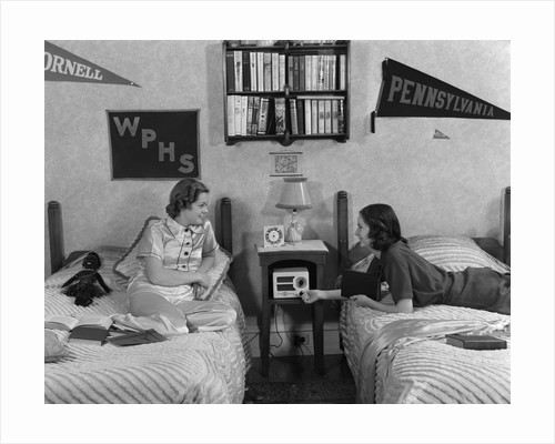 1930s 1940s Two Teen Girls Lying On Dormitory Beds Room Mates Listening To Radio College School Pennants On Wall by Corbis