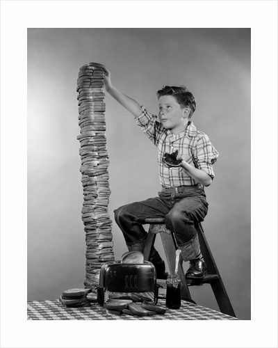 1950s Boy Eating Jelly Toast Sitting On Ladder Stacking Up Tall Pile Of Toast From Toaster by Corbis
