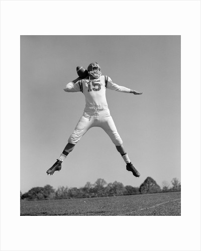 1960s Quarterback Jumping And Throwing Pass Football by Corbis