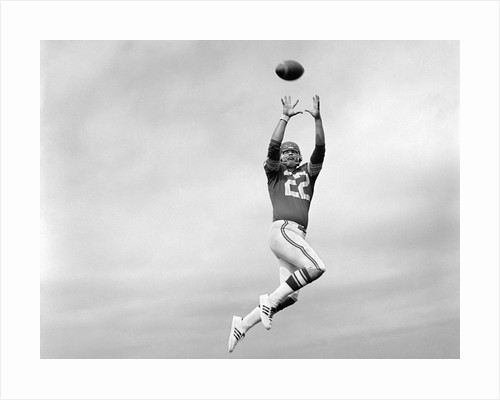 1970s Player Jumping To Catch Football Pass by Corbis