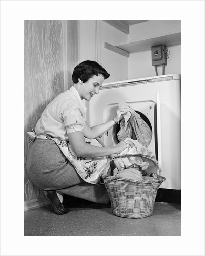 1950s Woman Kneeling Removing Clothes Laundry From Automatic Dryer by Corbis