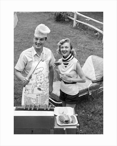 1950s Couple Backyard Grill Cook Hot Dogs Man Wearing Apron Toque and Skewered Hot Dog by Corbis