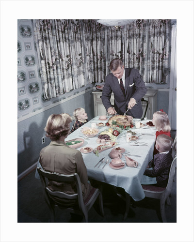 1950s Family 5 Sitting At Dining Room Table Dad Carves Turkey At Head Of Table by Corbis