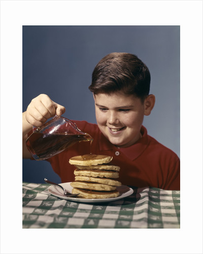 1950s 1960s Boy Pouring Syrup On Breakfast Pancakes by Corbis