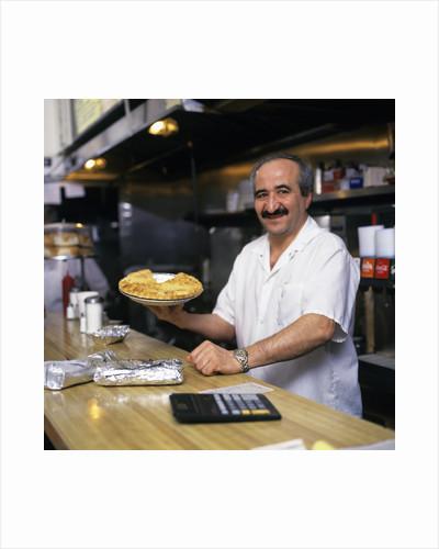 Portrait Man Working Behind Counter In Diner Holding Pie by Corbis