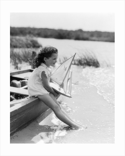 1930s Young Girl At Seashore Holding Sailboat Toy Sitting On Edge Of Rowboat Feet In Water by Corbis