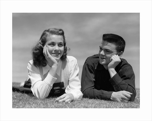 1950s Teenage Couple Laying On Grass, Boy Gazing At Girl Wearing Cheerleader Sweater by Corbis
