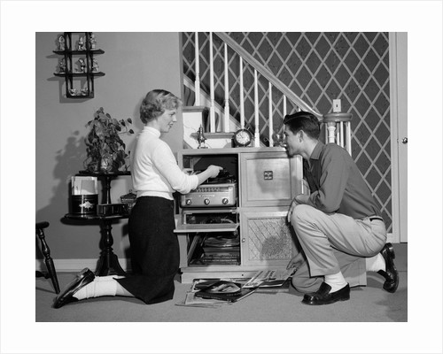 1950s Teenage Couple Playing Hi-Fi Records On Console Phonograph In Living Room by Corbis