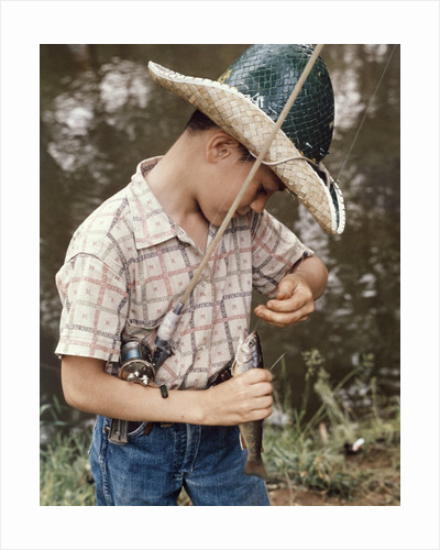 Boy Wearing Straw Hat Removing Hook From Mouth Of Fish Outdoor by Corbis