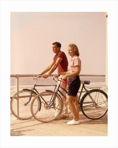 1950s 1960s Teen Couple Standing By Bikes On Beach Boardwalk by Corbis