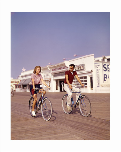 1950s Teen Couple Riding Bikes On The Boardwalk Jersey Shore by Corbis