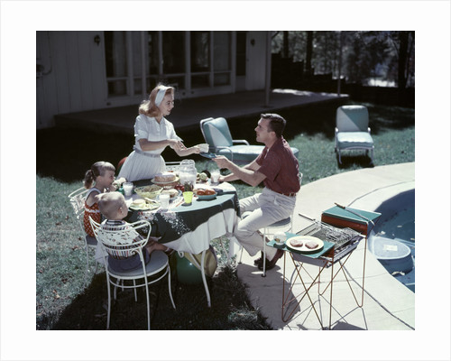 1950s Family In Backyard Having Picnic From Grill Near Swimming Pool by Corbis