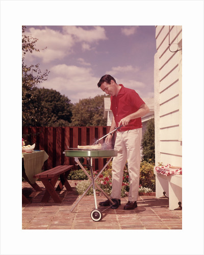 1960s Man Wearing Red Shirt Cooking Steak Outdoor On Backyard Grill by Corbis