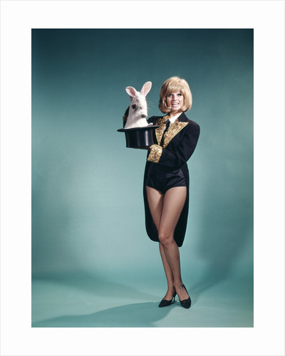 1960s Young Woman In Stage Magician Coat And Short Shorts Pulling Rabbit Out Of Top Hat by Corbis