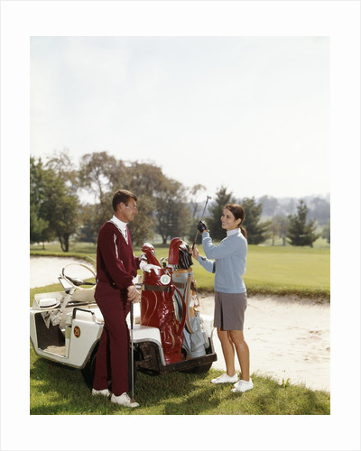 1960s Couple Man Woman Selecting Golf Clubs From Golf Bag On Cart By Sand Trap by Corbis
