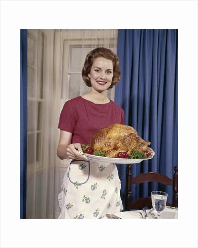 1960s Woman Serving Thanksgiving Turkey Dinner by Corbis