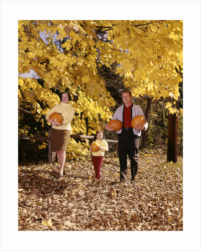 1960s Family Trio Father Mother Daughter Walking In Autumn Woods Carrying Pumpkins by Corbis