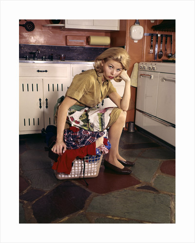1960s Weary Dejected Woman Housewife Homemaker Sitting On Full Laundry Basket In Kitchen by Corbis
