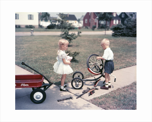 1950s Little Girl Sister Holding Doll Watching Little Boy Brother Repair Tricycle by Corbis